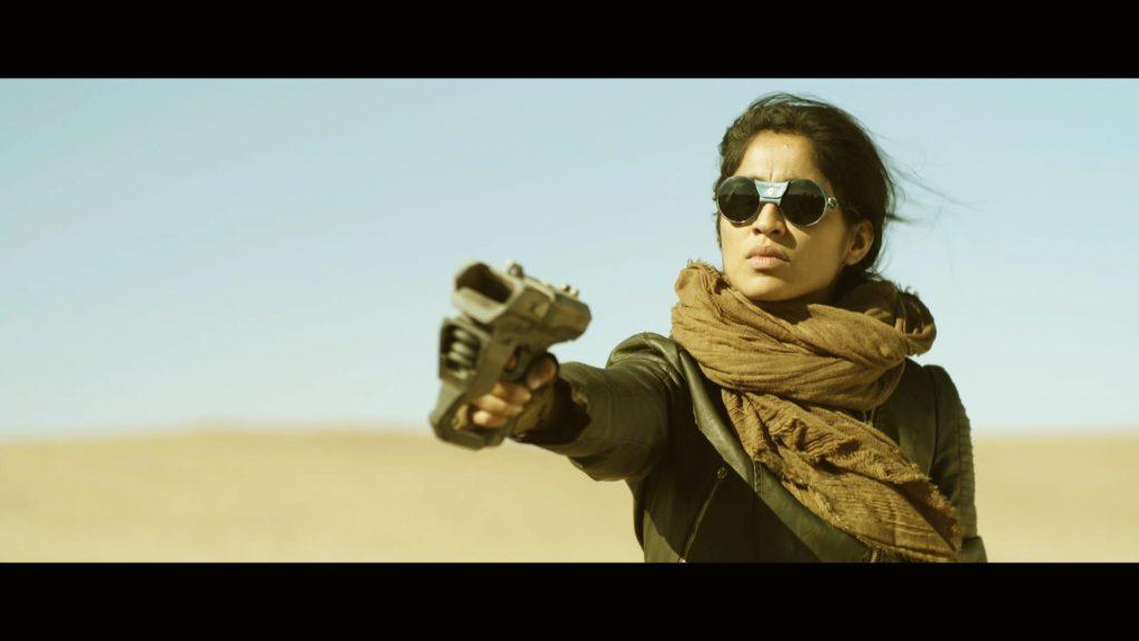Gabriela Paz Arancibia sostiene un arma futurista en un plano de una escena del cortometraje EL ULTIMO DESIERTO de Andrés Salva. Música de ruboc.